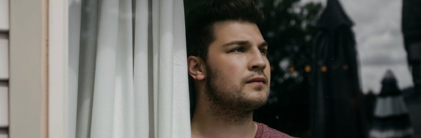 Man looking out the window during a real estate showing